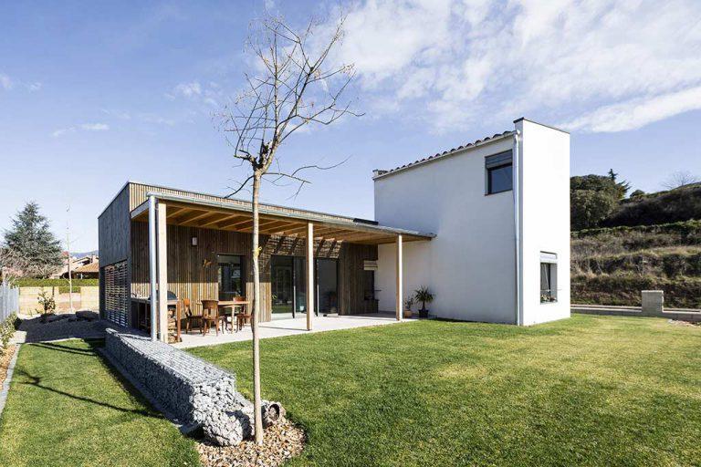 Vistes casa eficient amb porxo de fusta