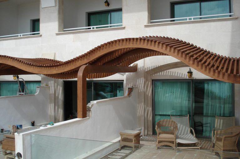 Porxo embigat de fusta en forma d'onades en habitacions hotel