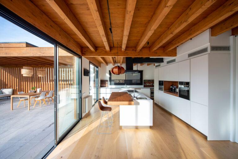 Cuina amb sostre embigat de fusta, parquet i taulell de la barra també en fusta.