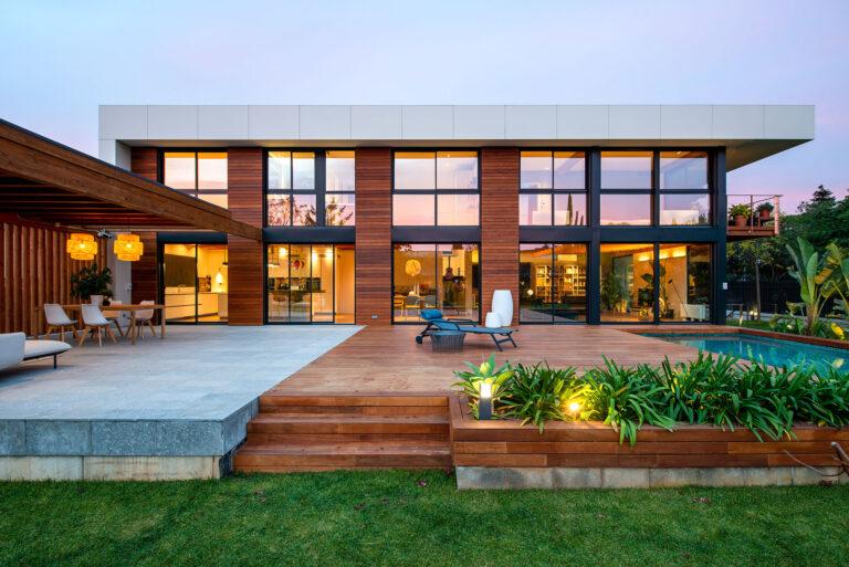 Vista de la casa des del costat del porxo de fusta i de la piscina. El terra que envolta la piscina també és de fusta així com la façana de la casa.