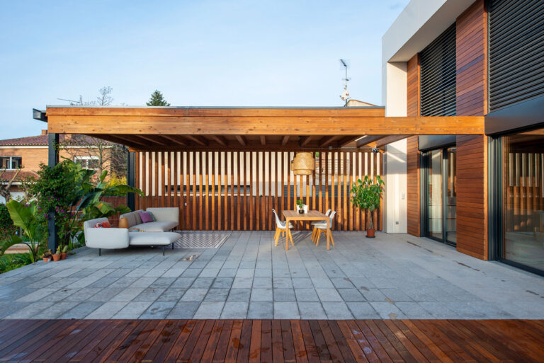 Vistes el porxo de fusta i d'un dels laterals de la casa eficient de Sant Cugat. La casa té grans obertures d'alumini amb persianes abatibles.