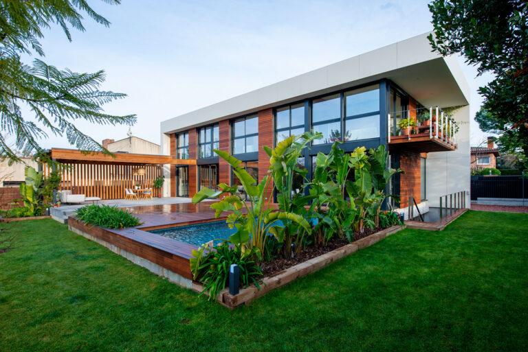 Vistes de la casa des de l'exterior. Es pot veure la piscina amb el terra de fusta, el porxo i dues façanes de la casa.