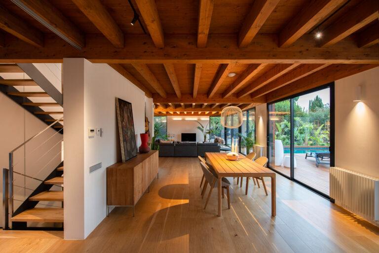 Vista del menjador de la casa. Es pot veure el terra en parquet i el sostre de fusta, combinat amb bigues.