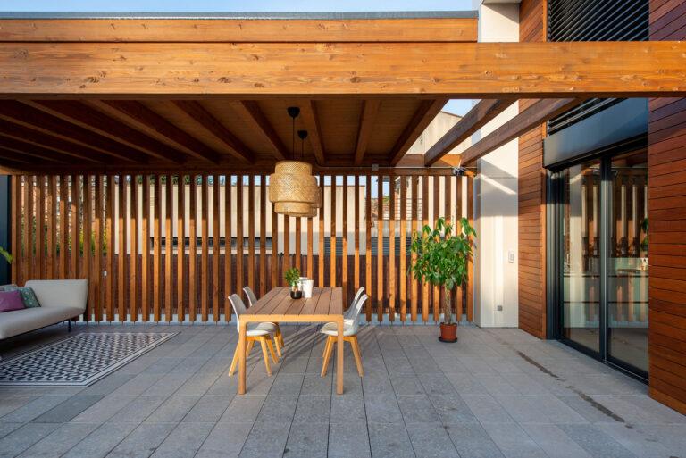 Vistes el porxo de fusta. Sostre de fusta amb bigues transversal i paret separadora amb columnes de fusta